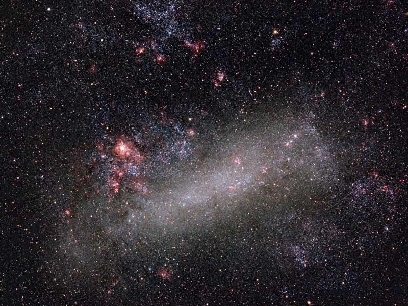 A Grande Nuvem de Magalhães, uma galáxia irregular. A mancha vermelha à esquerda é a região de formação estelar gigante 30 Doradus. Foto por Wei-Hao Wang.