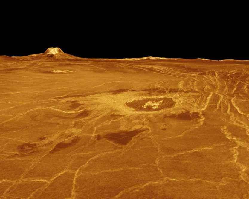Gula Mons e Cratera Cunitz  Uma parte de Eistla Regio Ocidental é mostrada nesta imagem tridimensional, em perspectiva, da superfície de Vênus. O ponto de vista está situado a 1.310 quilómetros a sudoeste de Gula Mons numa elevação de 0,78 quilômetros. O ponto de vista aponta para Noroeste, com Gula Mons aparecendo no horizonte. Gula Mons, um vulcão com 3 quilómetros de altura, está localizado aproximadamente a 22 graus Norte de latitude, 359 graus Este de longitude. A cratera de impacto Cunitz, nome da astrônoma e matemática Maria Cunitz, é visível no centro da imagem. A cratera tem 48,5 quilômetros de diâmetro e está a 215 quilômetros do ponto de vista do observador. (Cortesia NASA/JPL)