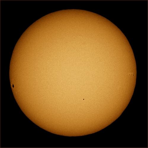 Trânsito de Mercúrio. Mercúrio é o pequeno ponto abaixo do centro, na frente do Sol. A área escura na esquerda do disco solar é umamancha.