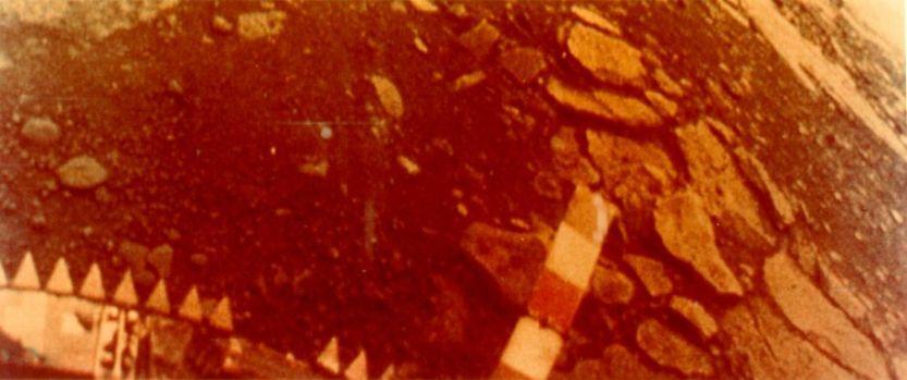 Fotografias Coloridas da Superfície pela Venera 13  A 1 de Março de 1982 a Venera 13 tocou na superfície de Vénus a 7,5 graus Sul, 303 graus Este, a Este de Phoebe Regio. Foi a primeira missão Venera a incluir uma câmara de televisão a cores. A Venera 13 resistiu na superfície por 2 horas e 7 minutos, tempo suficiente para obter 14 imagens. Esta imagem foi conseguida usando filtros de cor azul, verde e vermelho, com uma resolução de 4 a 5 minutos. Parte da sonda é visível na base da imagem. Estão visíveis lajes e solo. A verdadeira cor é difícil de avaliar, dado que a atmosfera de Vénus filtra a luz azul. A composição da superfície é semelhante ao basalto da Terra. No terreno ao fundo está a tampa da lente. Esta imagem é a metade esquerda da fotografia da Venera 13.