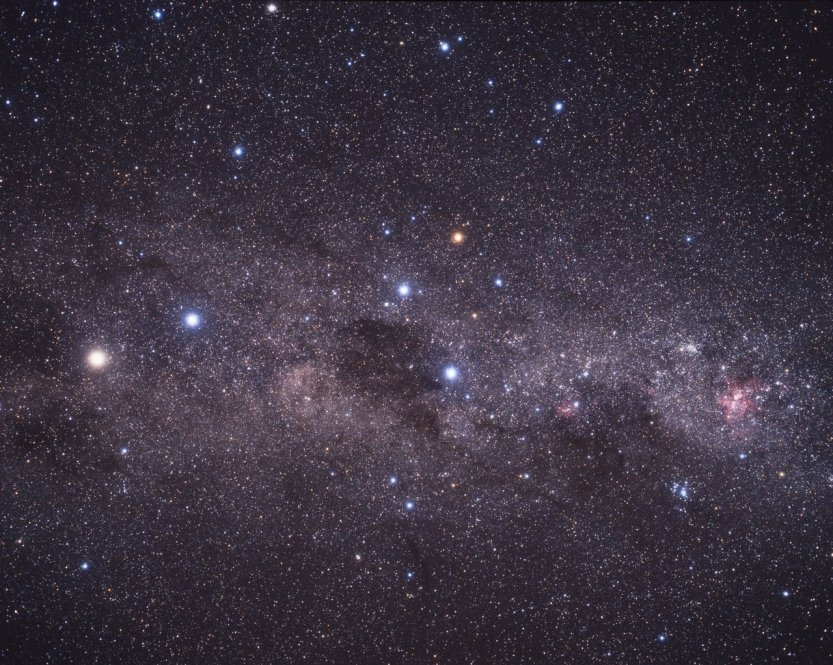 This wide-field image shows the Milky Way stretching across the southern sky. The beautiful Carina Nebula (NGC 3372) is seen at the right of the image glowing in red. It is within this spiral arm of our Milky Way that the bright star cluster NGC 3603 resides. At the centre of the image is the constellation of Crux (The Southern Cross). The bright yellow/white star at the left of the image is Alpha Centauri, in fact a system of three stars, at a distance of about 4.4 light-years from Earth. The star Alpha Centauri C, Proxima Centauri, is the closest star to the Solar System.
